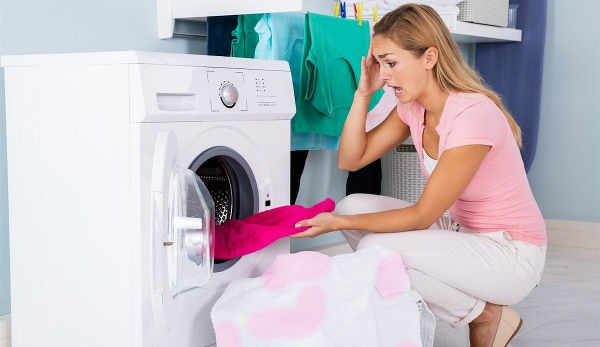 Worried woman pulling ruined clothing out of dryer