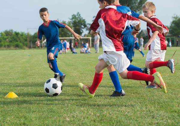 Children playing soccer on grass field