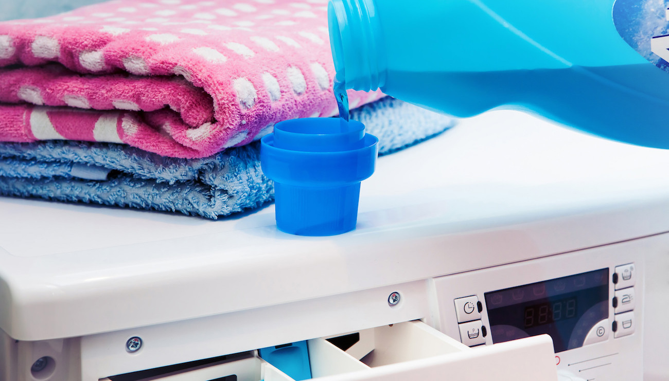 Person pouring liquid fabric softener in measuring cup to put into washing machine dispenser