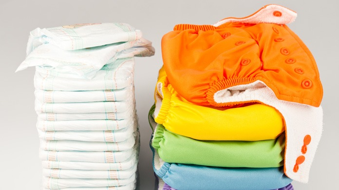 A stack of disposable diapers next to a stack of colorful cloth diapers