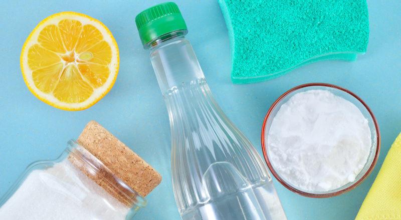 Flatlay of vinegar, baking soda, borax, a sponge and a lemon for making DIY laundry products