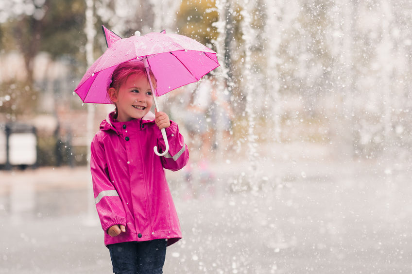 Child wearing a pink raincoat and holding a pink umbrella in the rain.