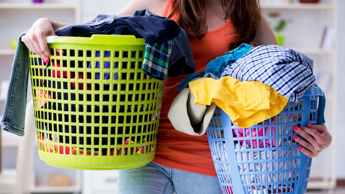 Stressed college student holding two baskets full of dirty laundry