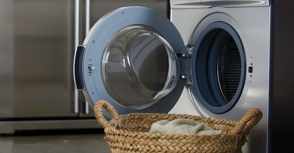 Silver washer with door open and laundry basket in front