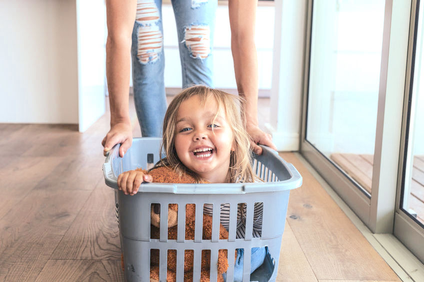 Child in a laundry basket smiling.
