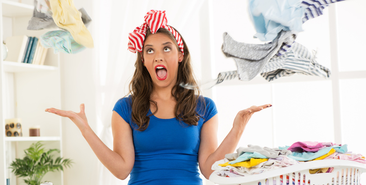 Frustrated woman throwing dirty laundry up in the air