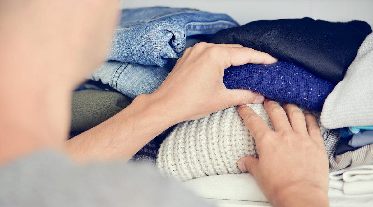 Woman putting winter sweaters away on shelf