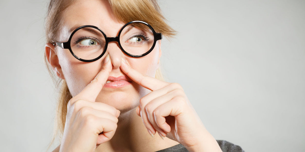 Woman pinching her nose because of an unpleasant odor