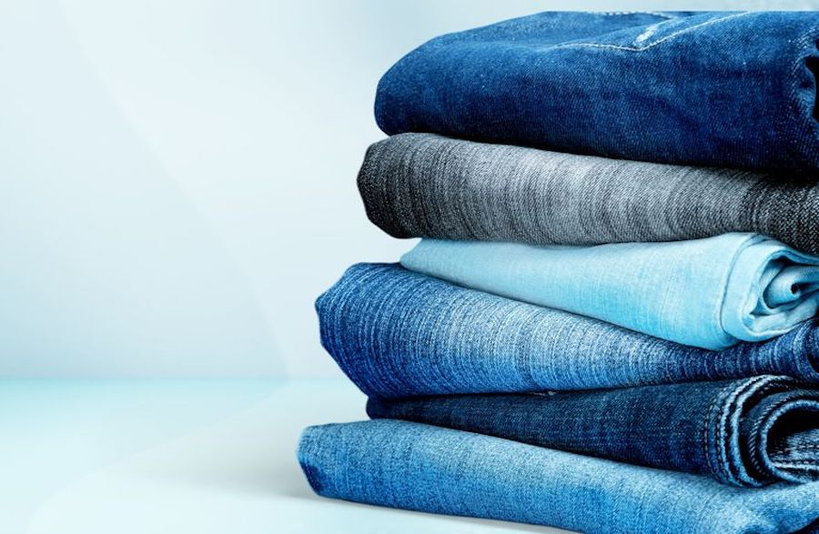 Close up of several pairs of denim jeans neatly folded in a stack.