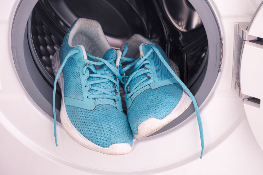Close up of blue sneakers inside washing machine