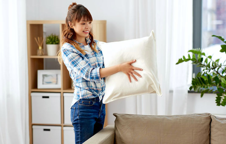 Woman smiling and fluffing a pillow in living room