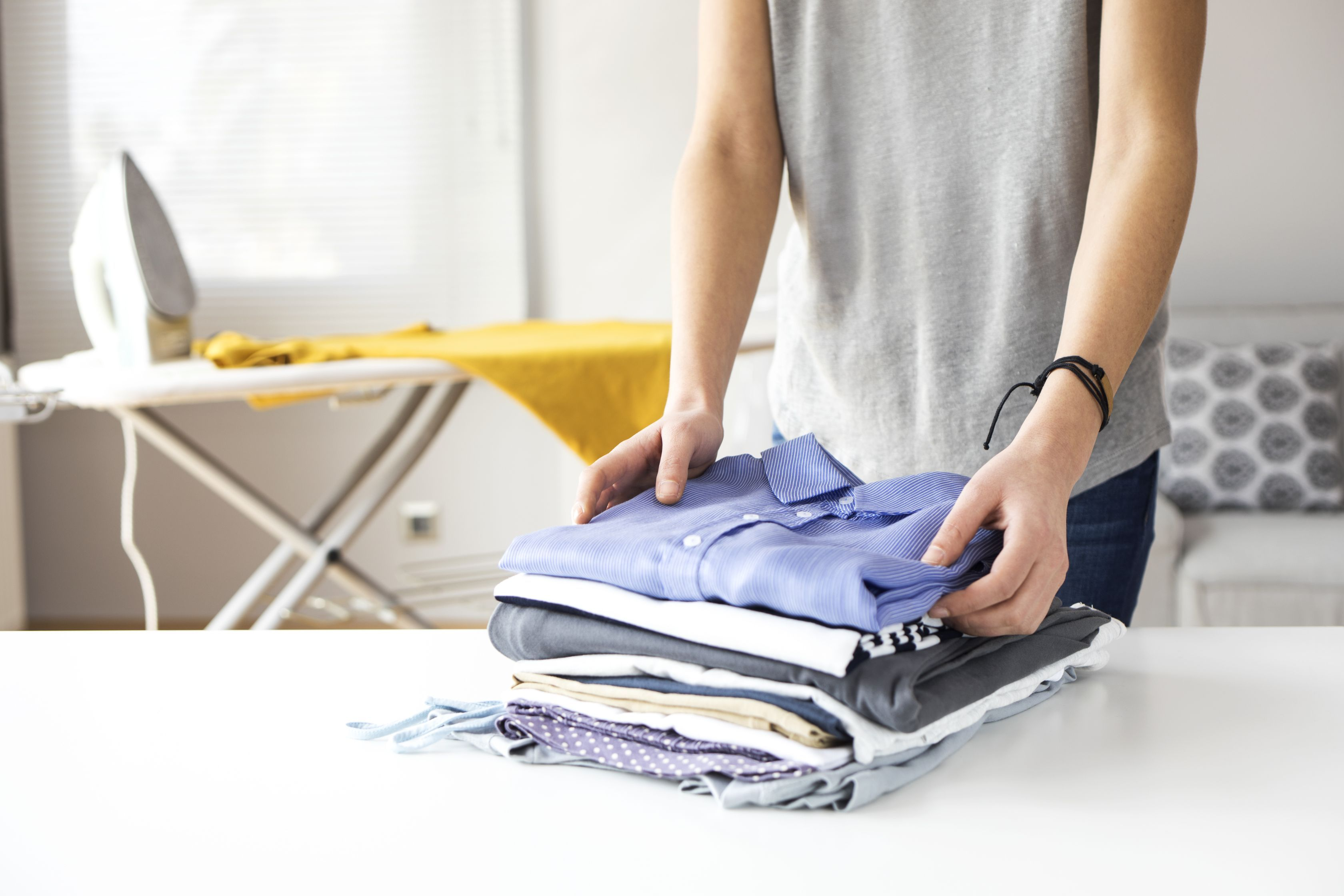 Person neatly folding and stacking clean clothes on a white table