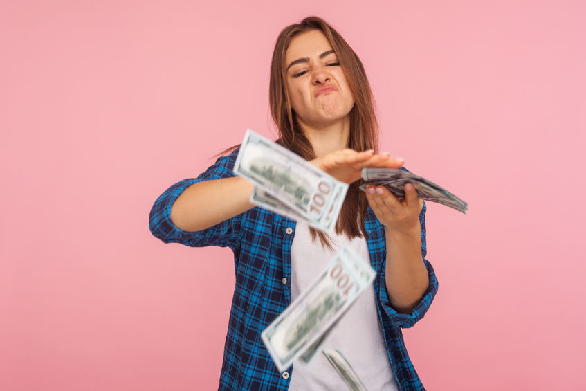 Wealthy young woman throwing dollars out on pink background