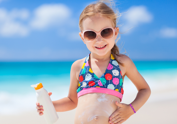 Little girl at the beach holding a bottle of sunscreen and applying it to her stomach.